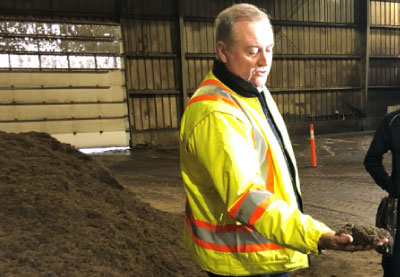 ottowa composting facility man holding some completed compost
